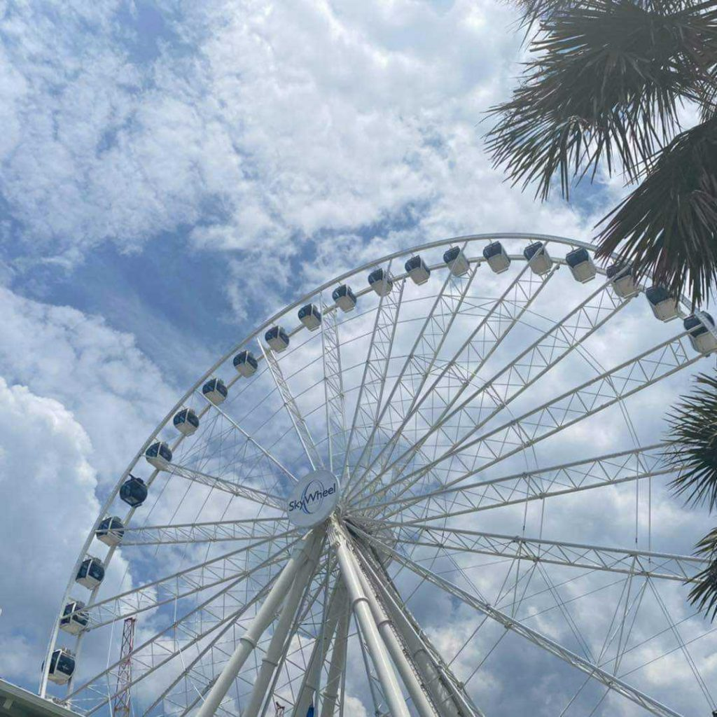 Clouds in sky with Myrtle Beach SkyWheel and gondolas.