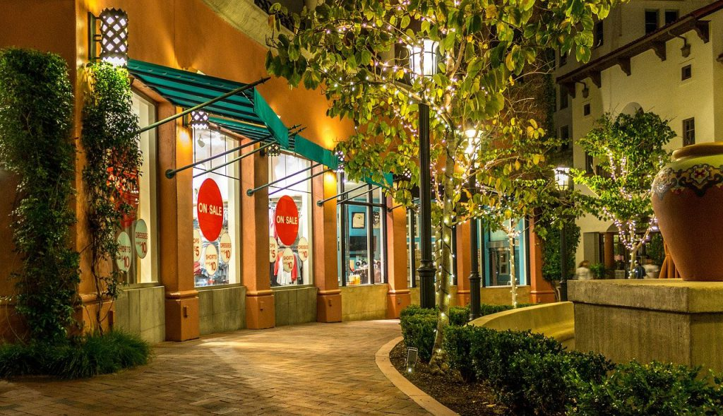 outdoor shopping mall, store, green awnings, trees, light poles, sale sticker in windows, bushes on right side,
