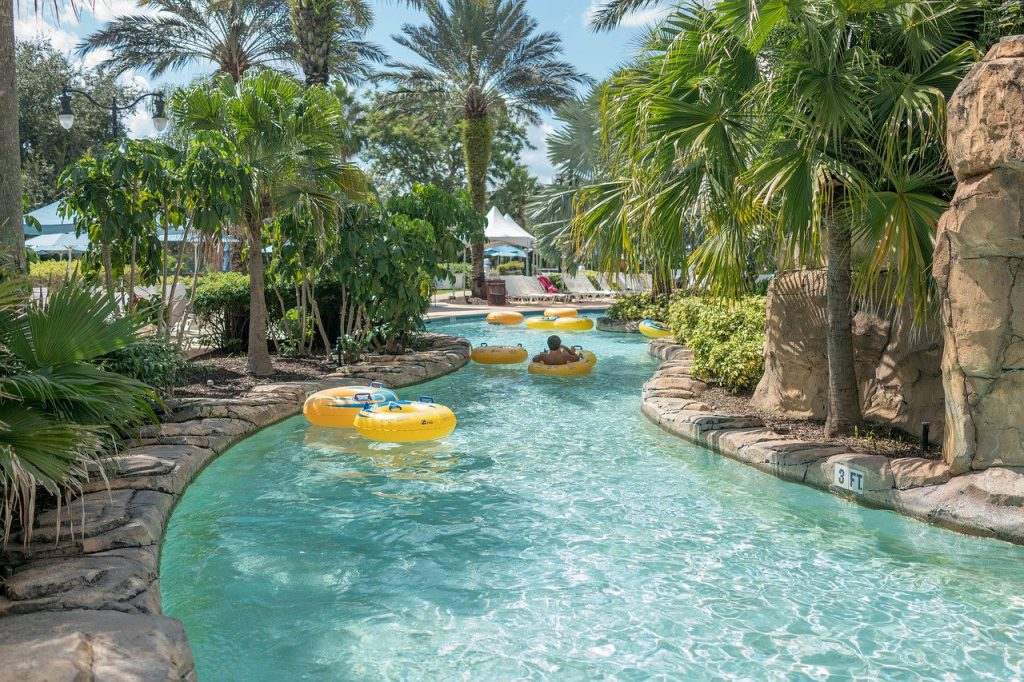 lazy river, pool water, yellow inner tubes with blue handles, palm trees, rocks, boy on tube